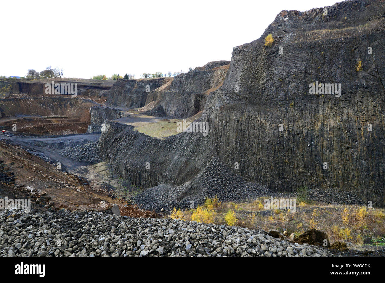 The basalt pit Bauersberg. Rhoen, Bavaria, Germany. Pit with mining area. Rock structures recognizable - Stock Image