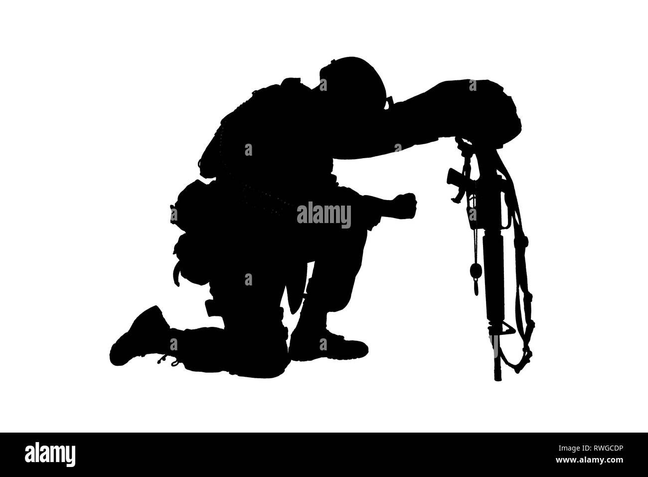 Silhouette of a soldier kneeling in respect for a fallen comrade. - Stock Image