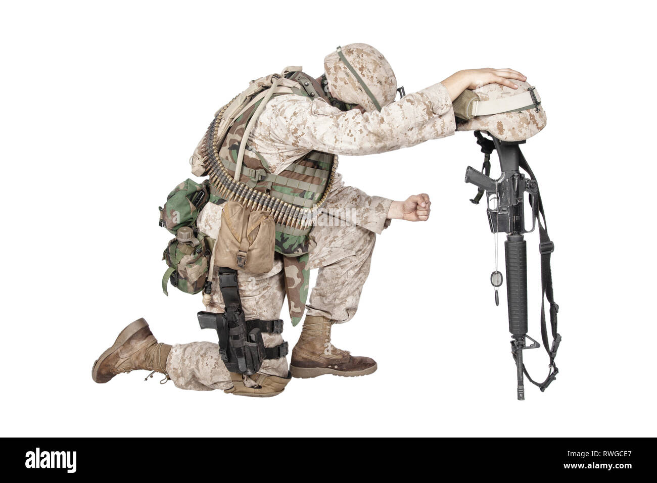 Soldier kneeling and leaning on rifle with helmet in respect for a fallen comrade. - Stock Image