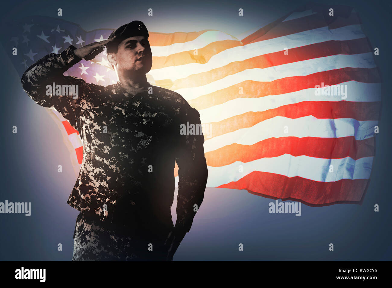 U.S. soldier standing at attention saluting proudly with honor and respect to his country. - Stock Image