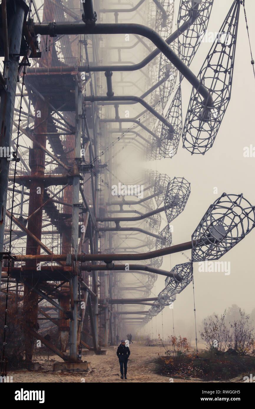 Man walks under the Duda Radar inside Chernobyl Exclusion Zone - Stock Image