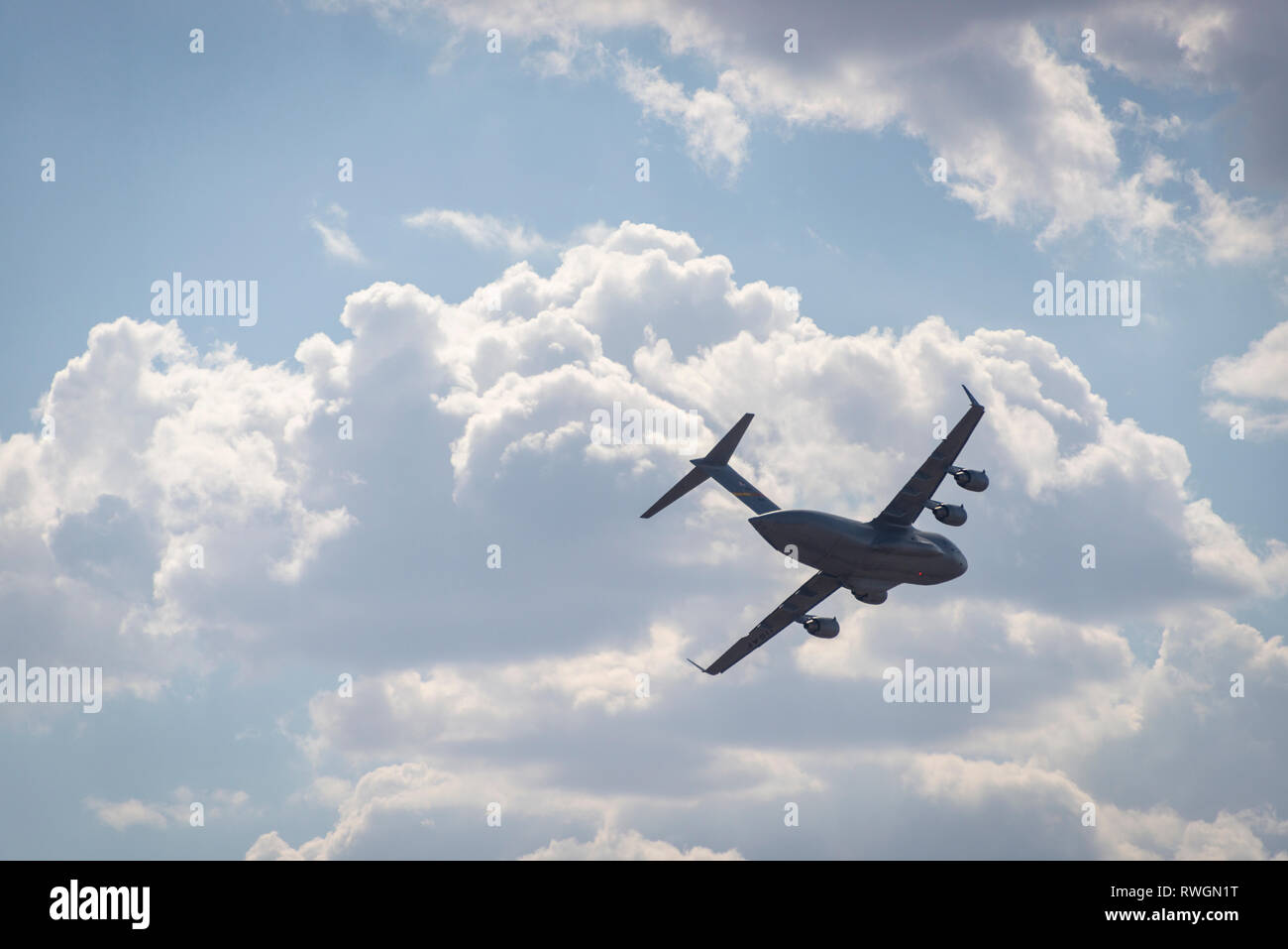 A Boeing C-17 Globemaster III in flight, banking against a cloudy sky - Stock Image