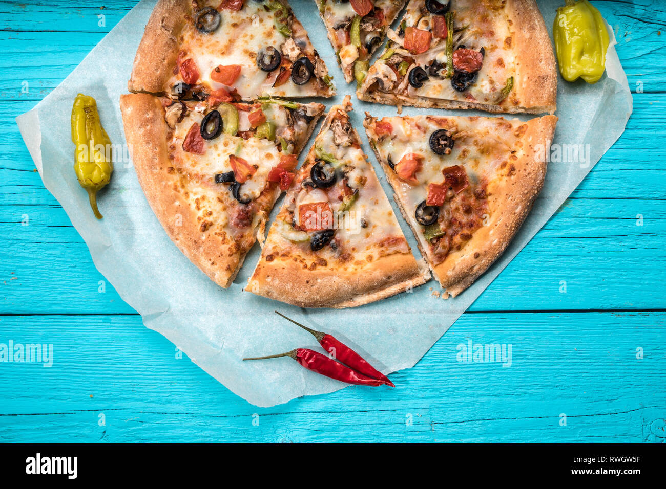 Vegetarian pizza with vegetables on blue table. - Stock Image