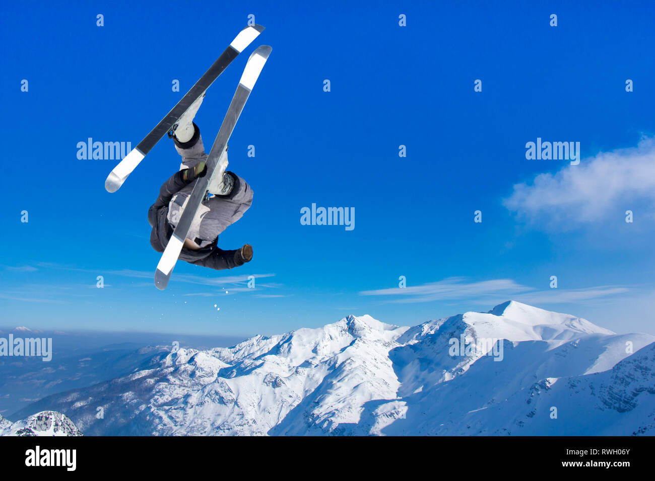 Extreme Jumping skier at jump above mountains at sunny day - Stock Image