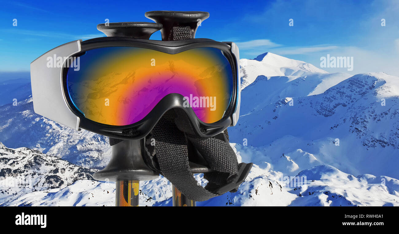 Close up of the ski goggles through which it is seen snowed mountains - Stock Image