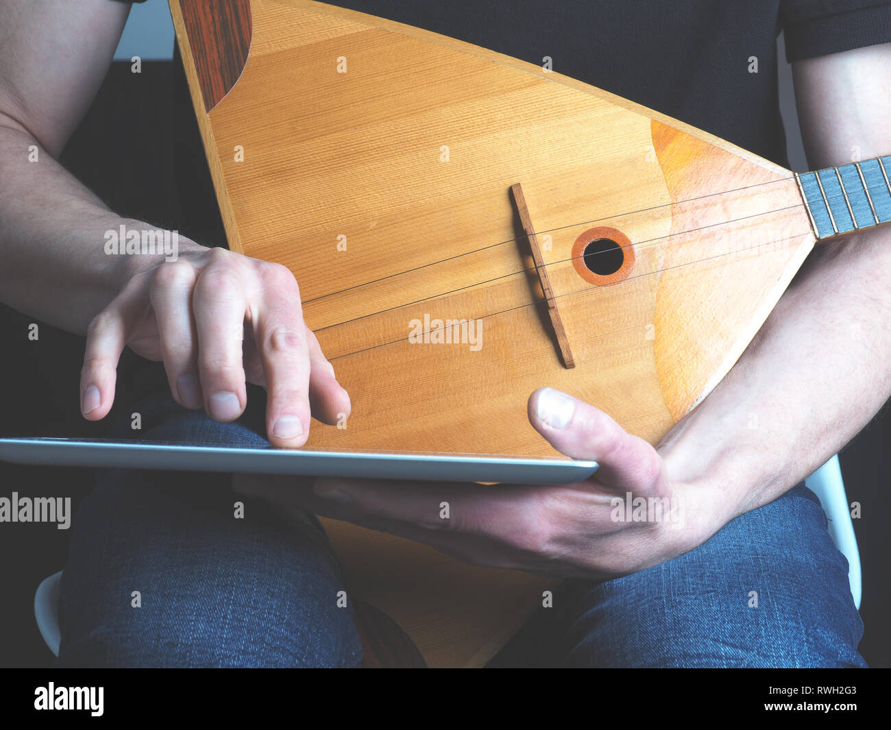Young musician with a balalaika using a tablet computer - Stock Image