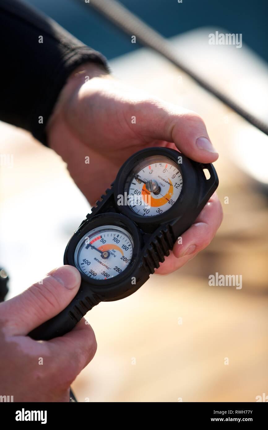 Extreme Close up of Diver's hands checking oxygen gauge regulator on board boat - Stock Image