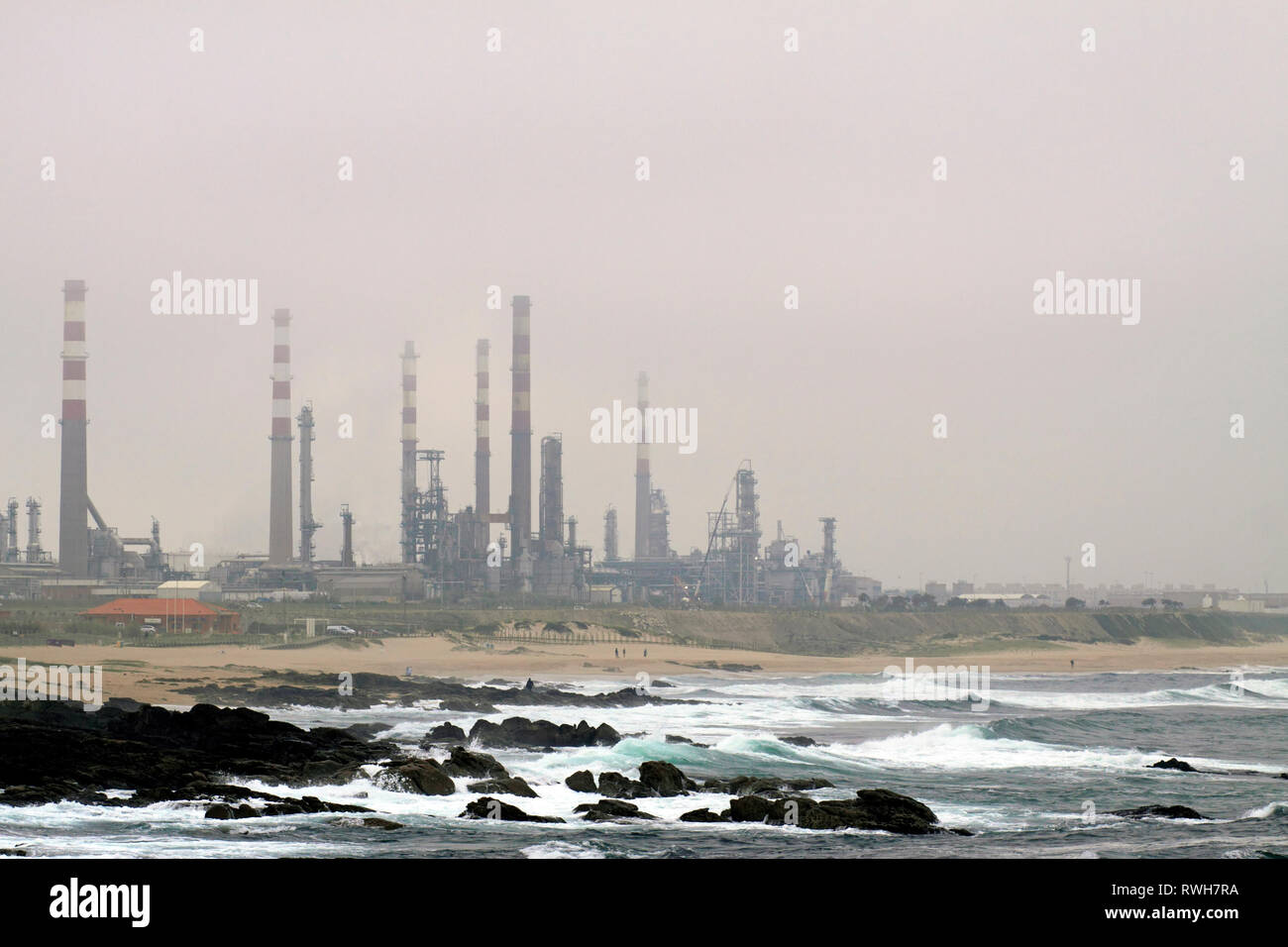 Oil refinery near the sea in a mysty late evening - Stock Image