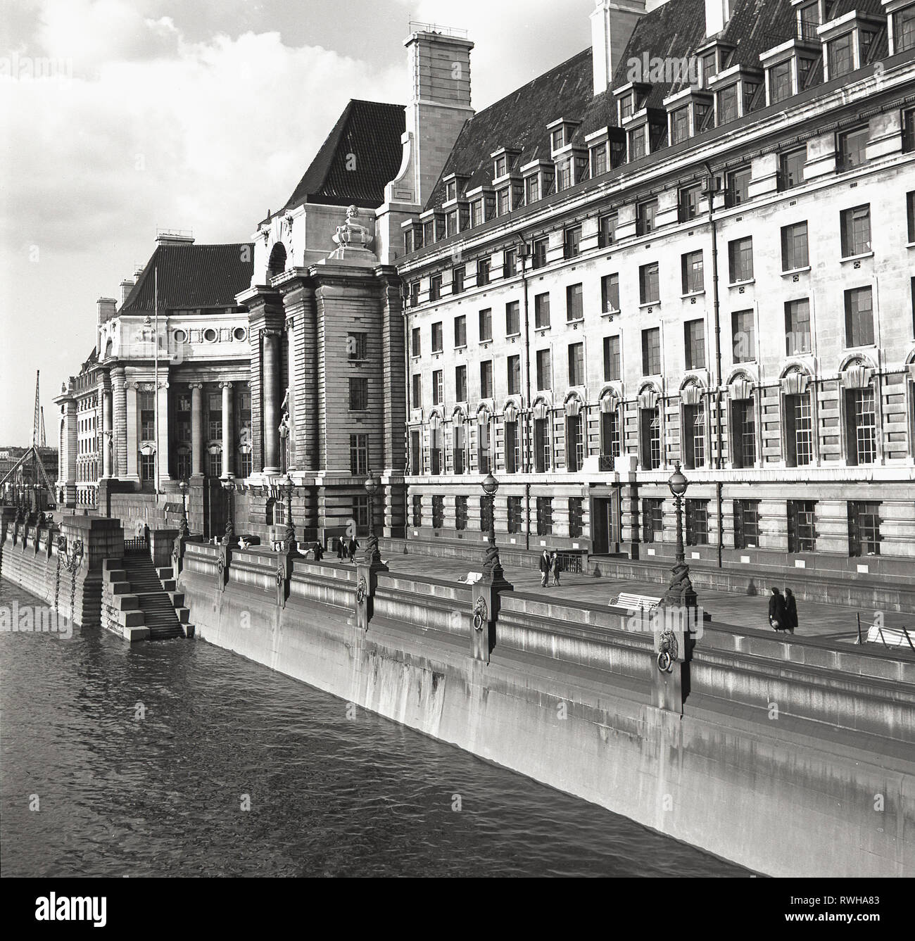 1950s, view from Westminster Bridge of County Hall, overlooking the river Thames, on the South Bank of London. At this time the offices of the LLC, the 'London County Council' and then from 1965, the GLC,,'Greater London Council'. The LCC was the principal local government body for the county of London and was the largest and most progressive English municipal authority of its day. - Stock Image