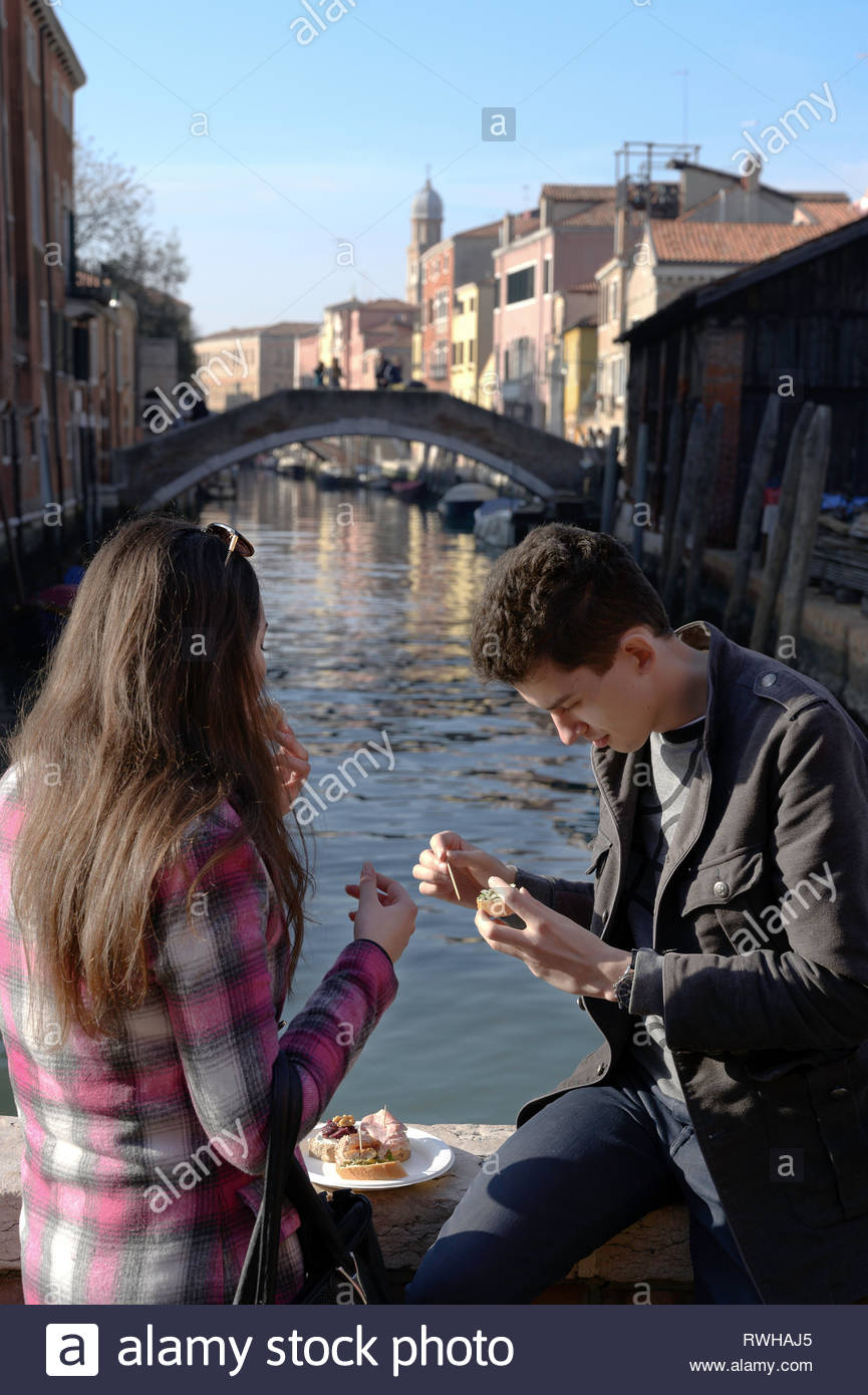 Couple eating an relaxing in the Vencie,near channel - Stock Image