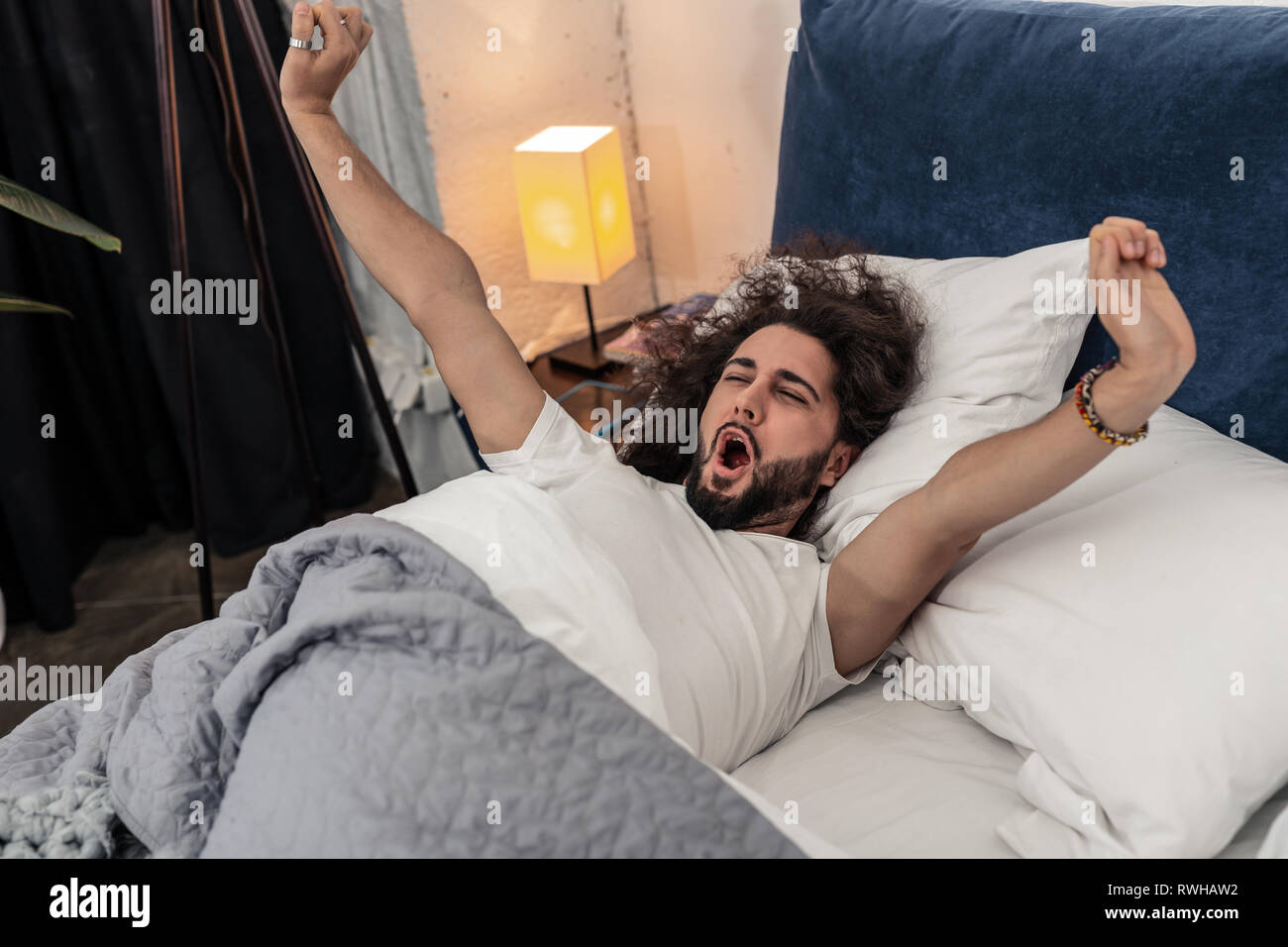 Nice handsome man lying in his comfortable bed - Stock Image
