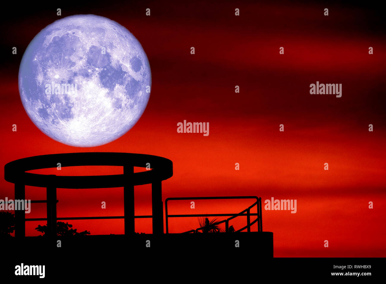 blue moon back over silhouette cycle on roof of building and night red sky, Elements of this image furnished by NASA - Stock Image