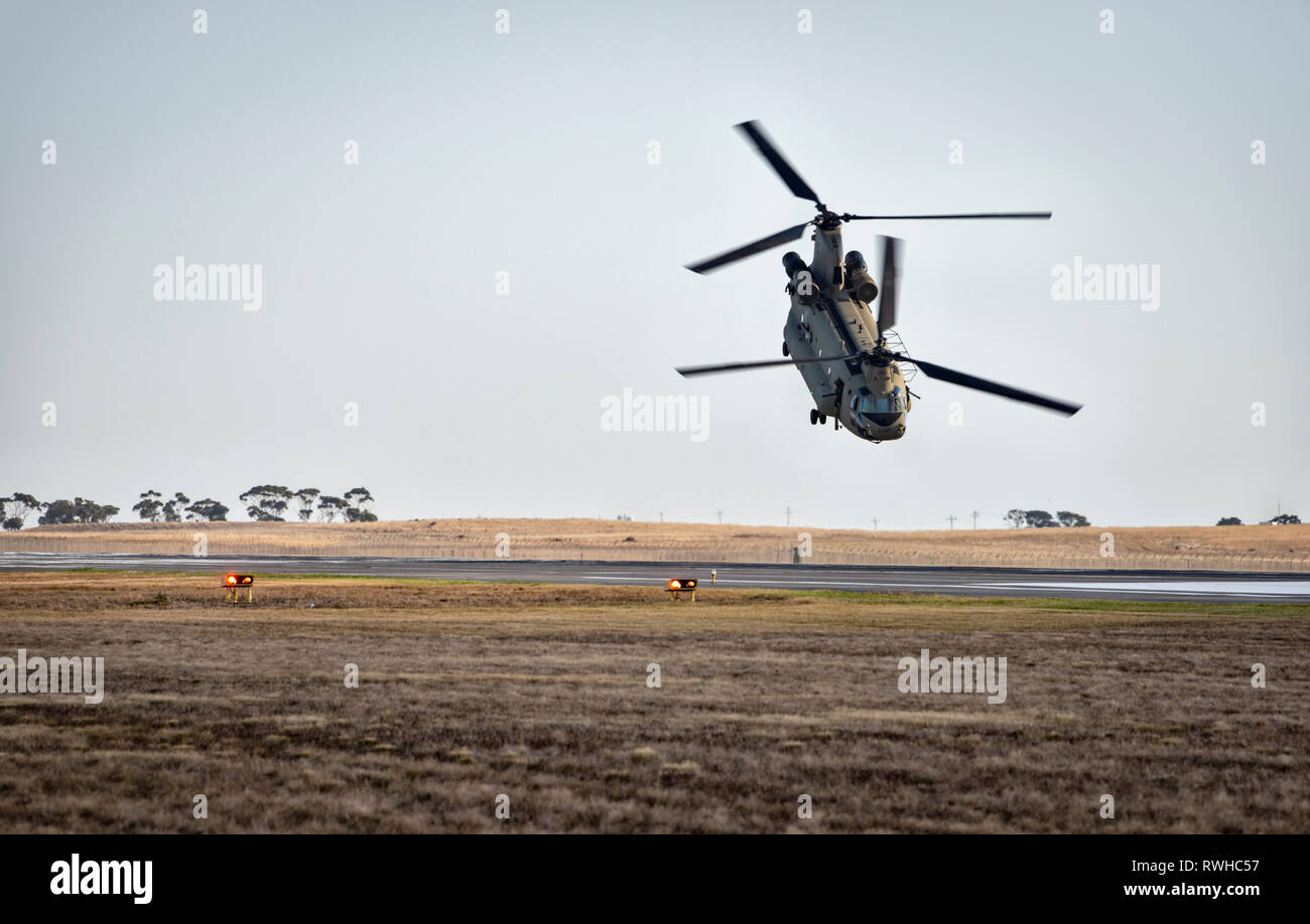 Boeing CH-47 Chinook helicopter taking off after dropping of ground support - Stock Image