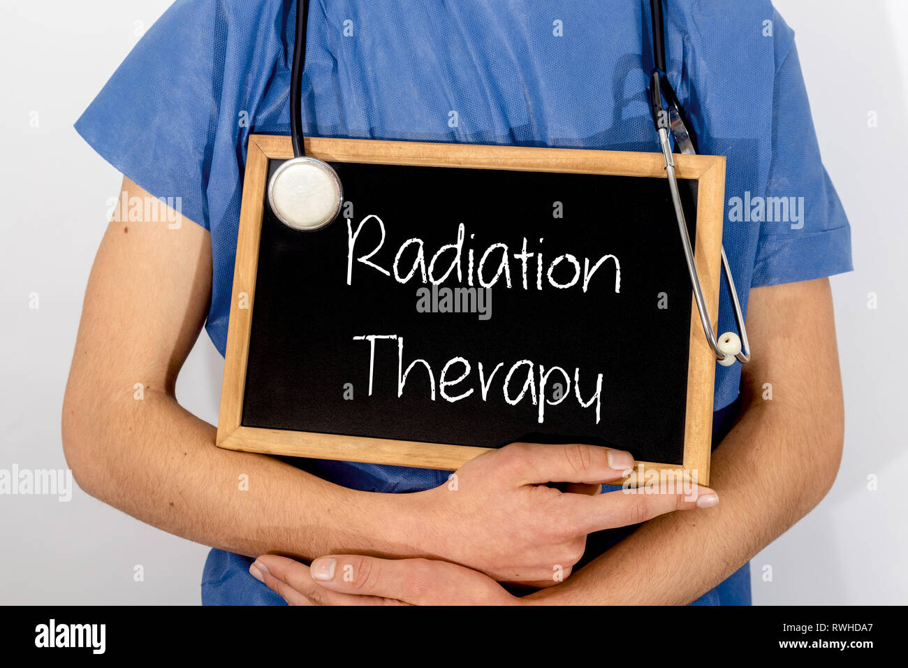 Doctor shows information on blackboard: radiation therapy.  Medical concept. - Stock Image
