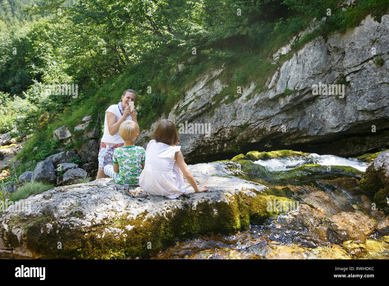 Mother taking a snapshot of kids on a family trip by a mountain stream. Outdoor lifestyle, positive parenting, childhood experience concept. - Stock Image