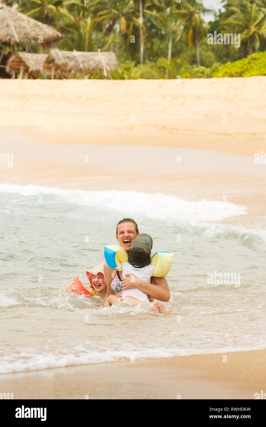 Mother enjoying a tropical beach, playing in the waves with her children. Travelling with children, beach hopping, family time, beach fun concept. Stock Photo