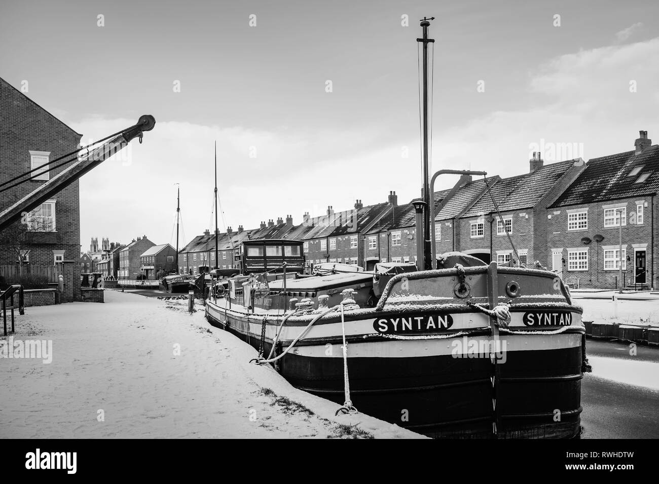 Vintage barges moored along the frozen beck (canal) and covered in snow flanked by town houses in Beverley, Yorkshire, UK. - Stock Image