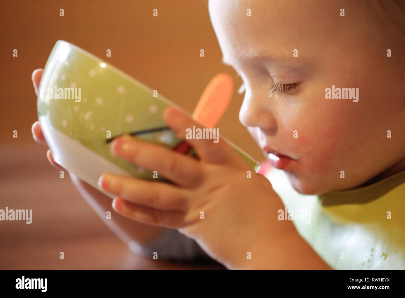 Little boy drinking independently from a bowl, feeding himself, making a mess. Early childhood development, milestones and progress, experience-based  - Stock Image