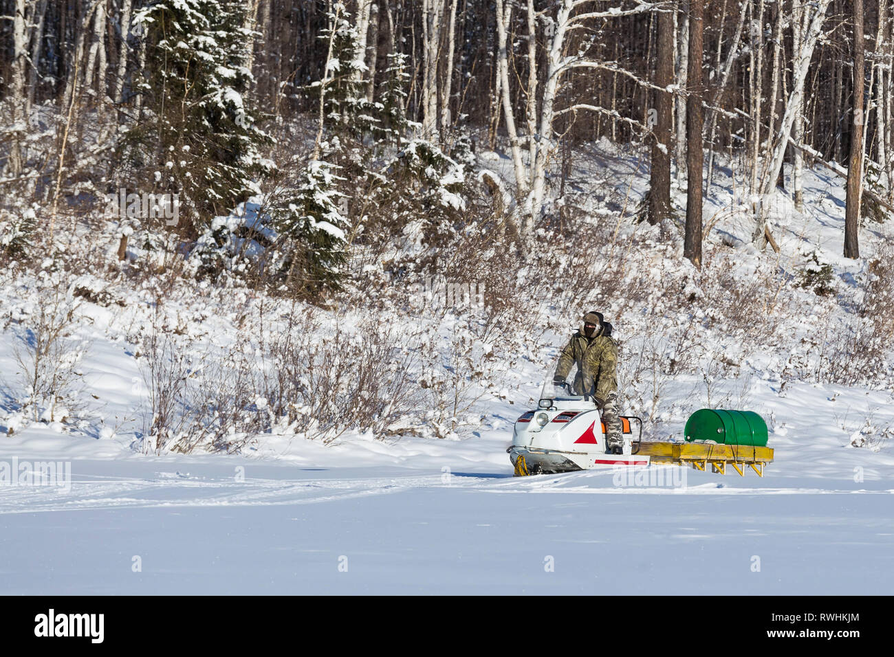 Nerungry, Neryungry District, Yakutia, Russia. January 29, 2017 Man carrying barrels of fuel on a snowmobile - Stock Image