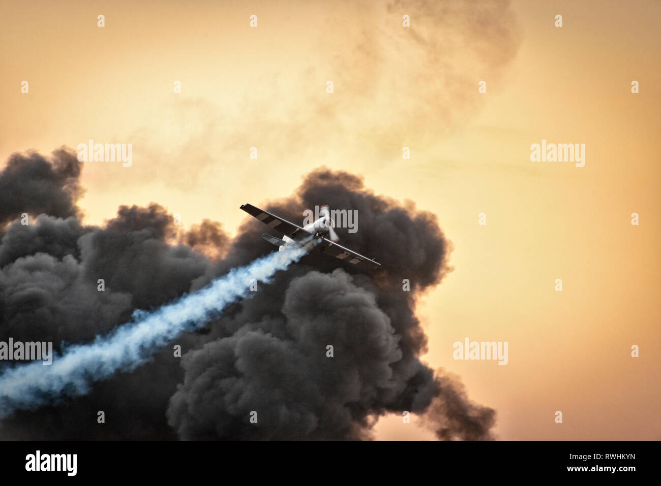 Yak-50 aerobatic plane flying through a cloud of smoke at an airshow - Stock Image