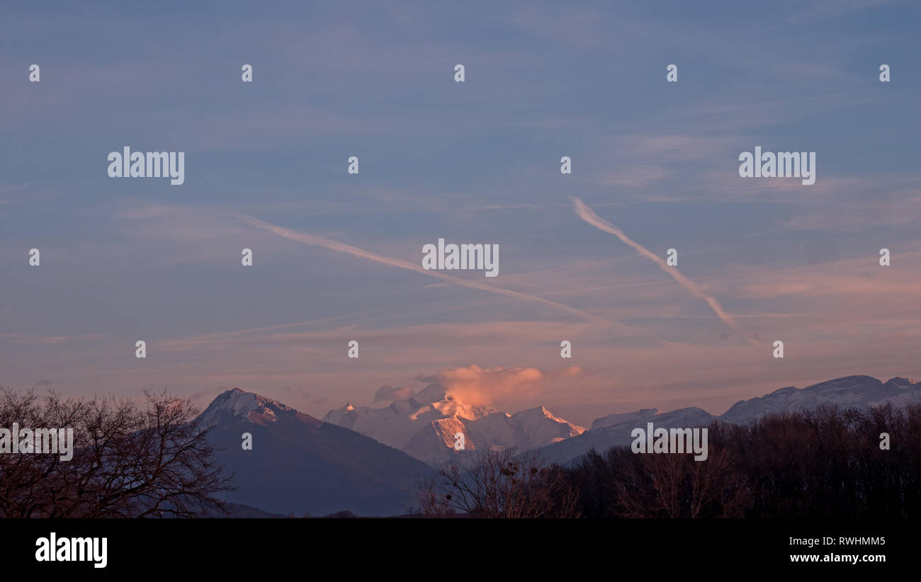 The highest mountain in Europe turns pink in the sunset as the clouds gather around the high snowy alpine peak. Stock Photo