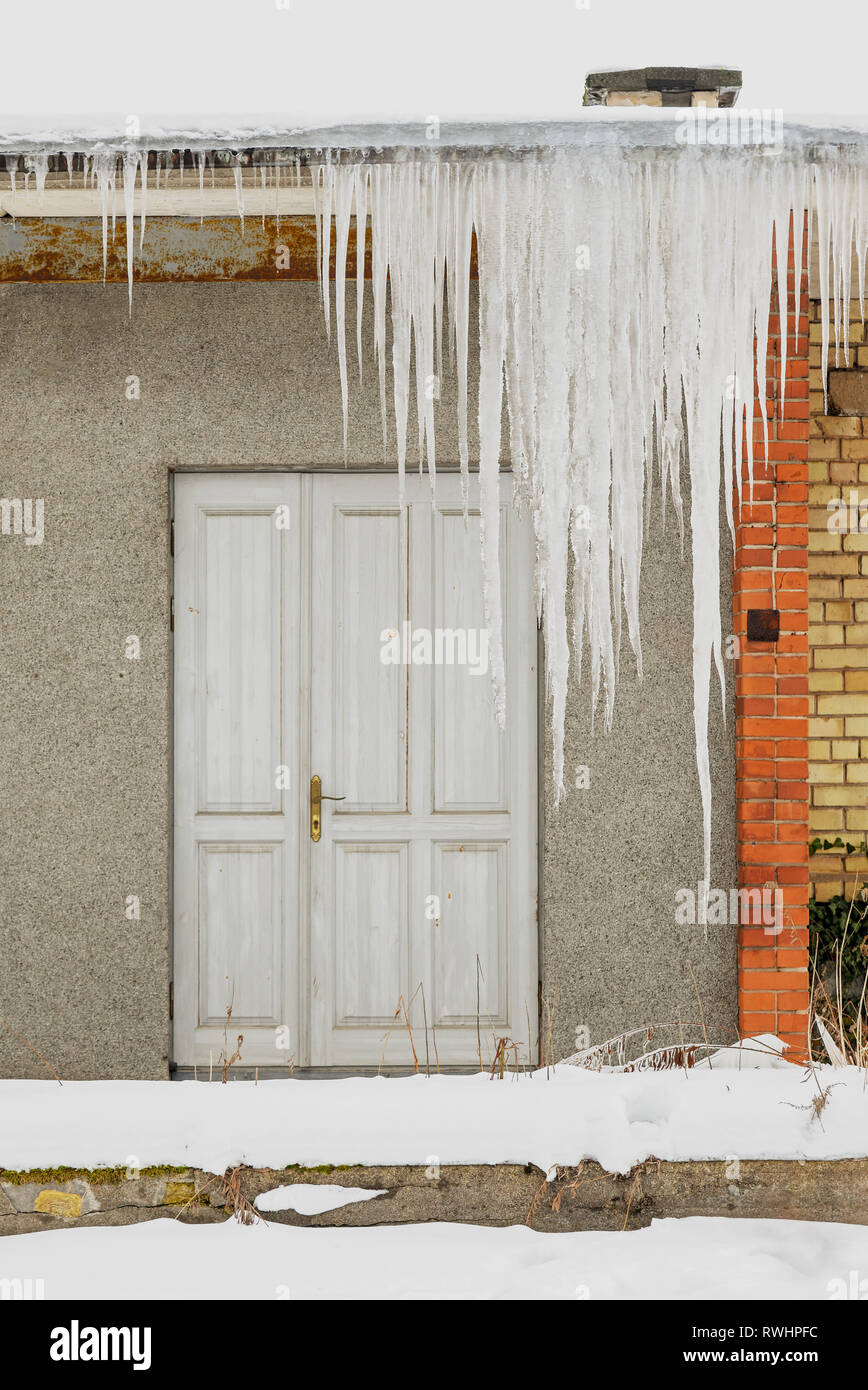 Huge icicles hang from the roof of an abandoned house with wooden door. Stock Photo