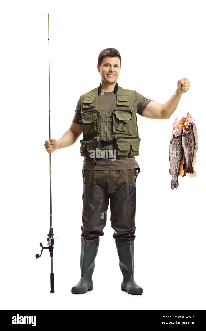Full length portrait of a young fisherman posing with a fishing rod and fish isolated on white background - Stock Image