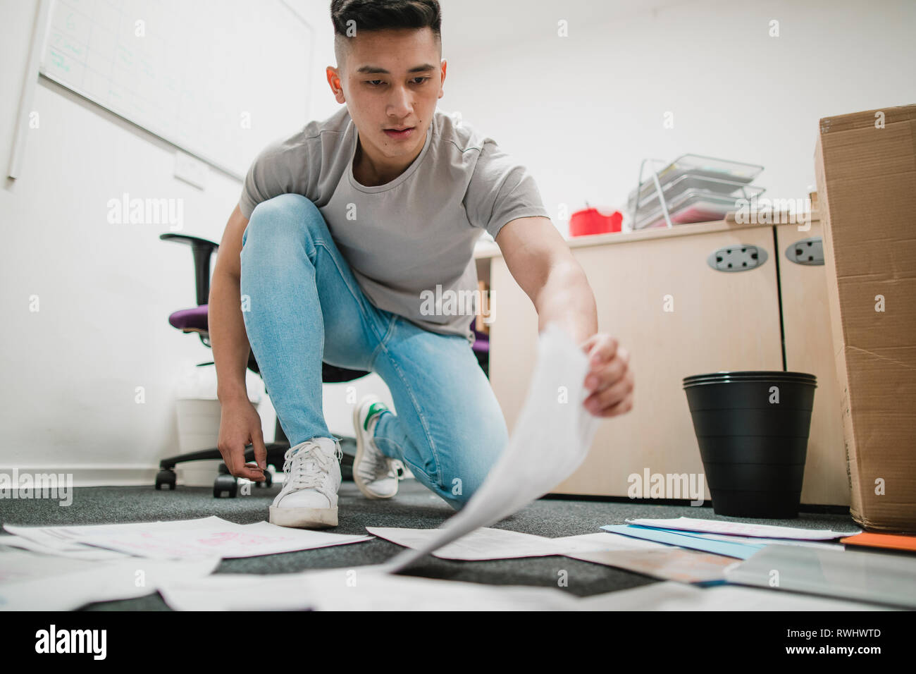 Young trainee is laying out paperwork on the floor in an office. - Stock Image