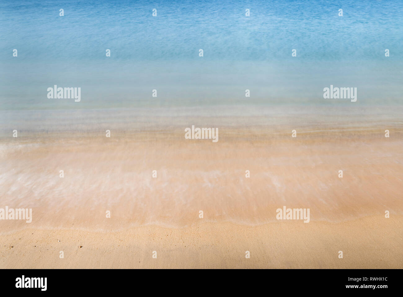 Abstract photo of motion blur of wave crashing on sand at a sandy beach - Stock Image