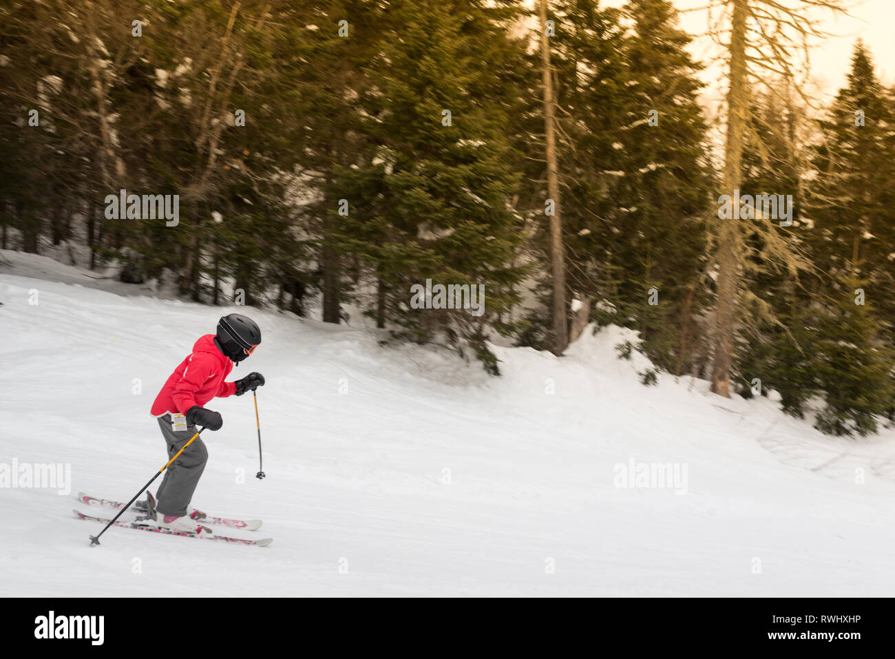 a6304f6557b1 Child wearing winter sports gear skis down a mountain Stock Photo ...
