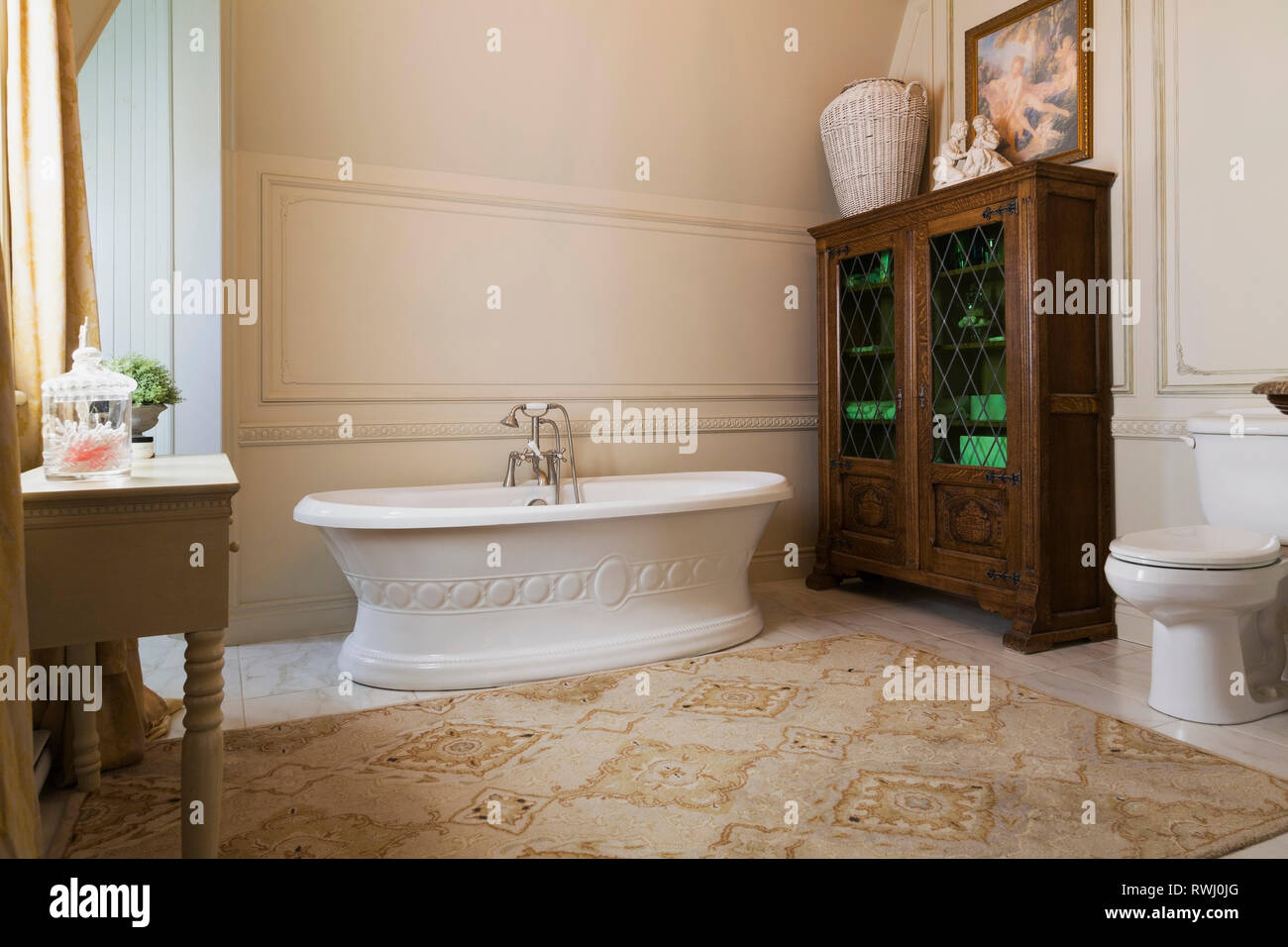 Freestanding boat style bathtub and wooden cabinet with leaded glass panels in the master bathroom on the upstairs floor inside a 2006 reproduction of - Stock Image
