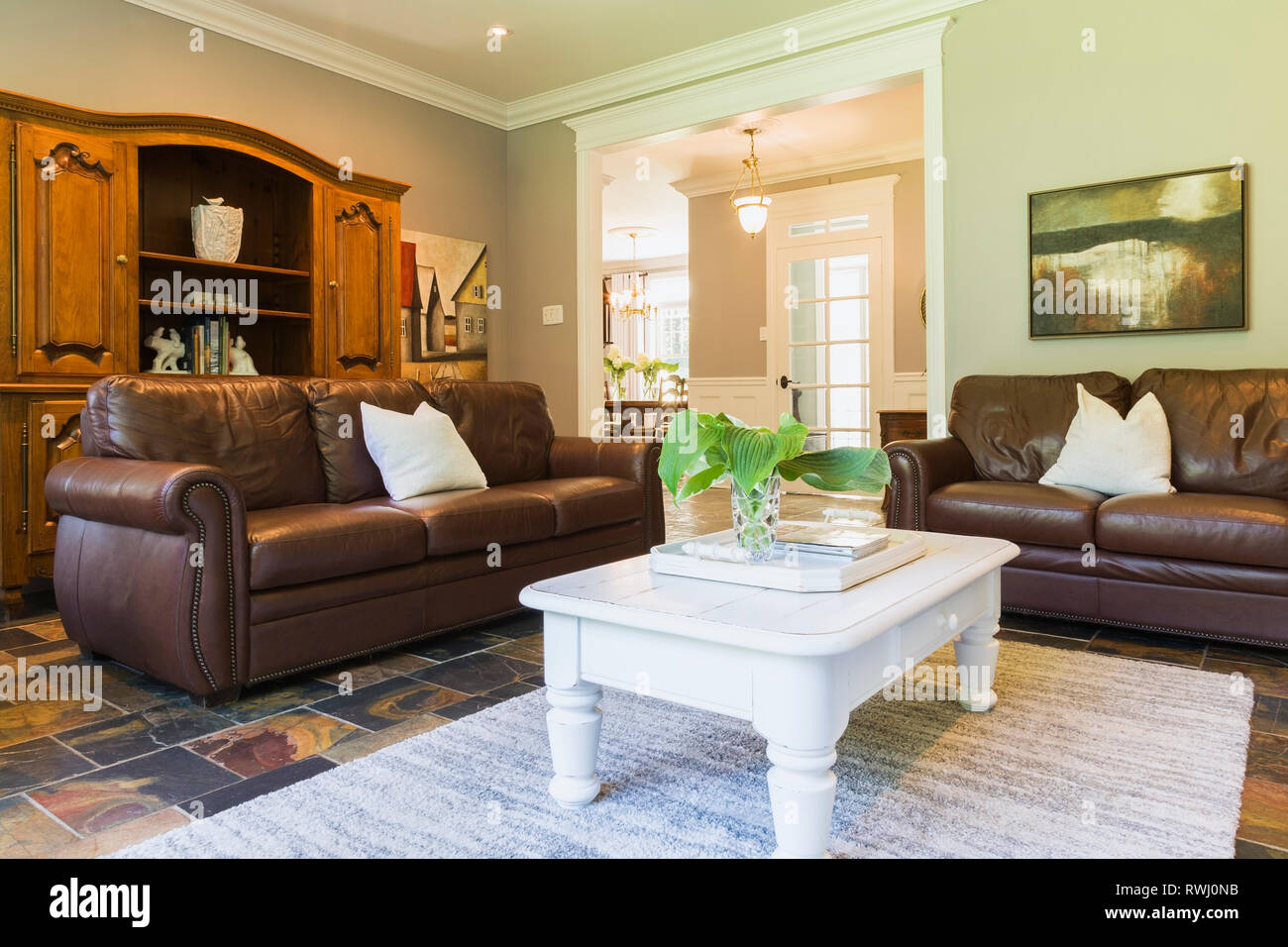 White wooden coffee table with brown leather sofas and ...