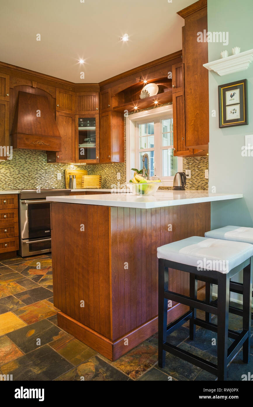 Kitchen with earth tone slate flooring, cherrywood cabinets ...