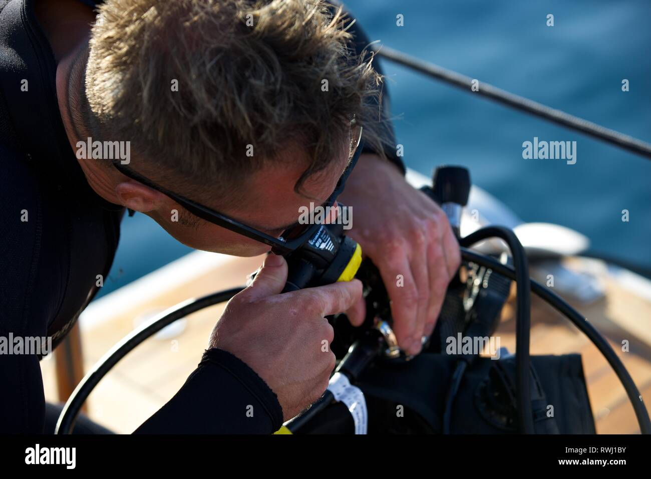 Close up of Diver checking respirator on board boat deck - Stock Image