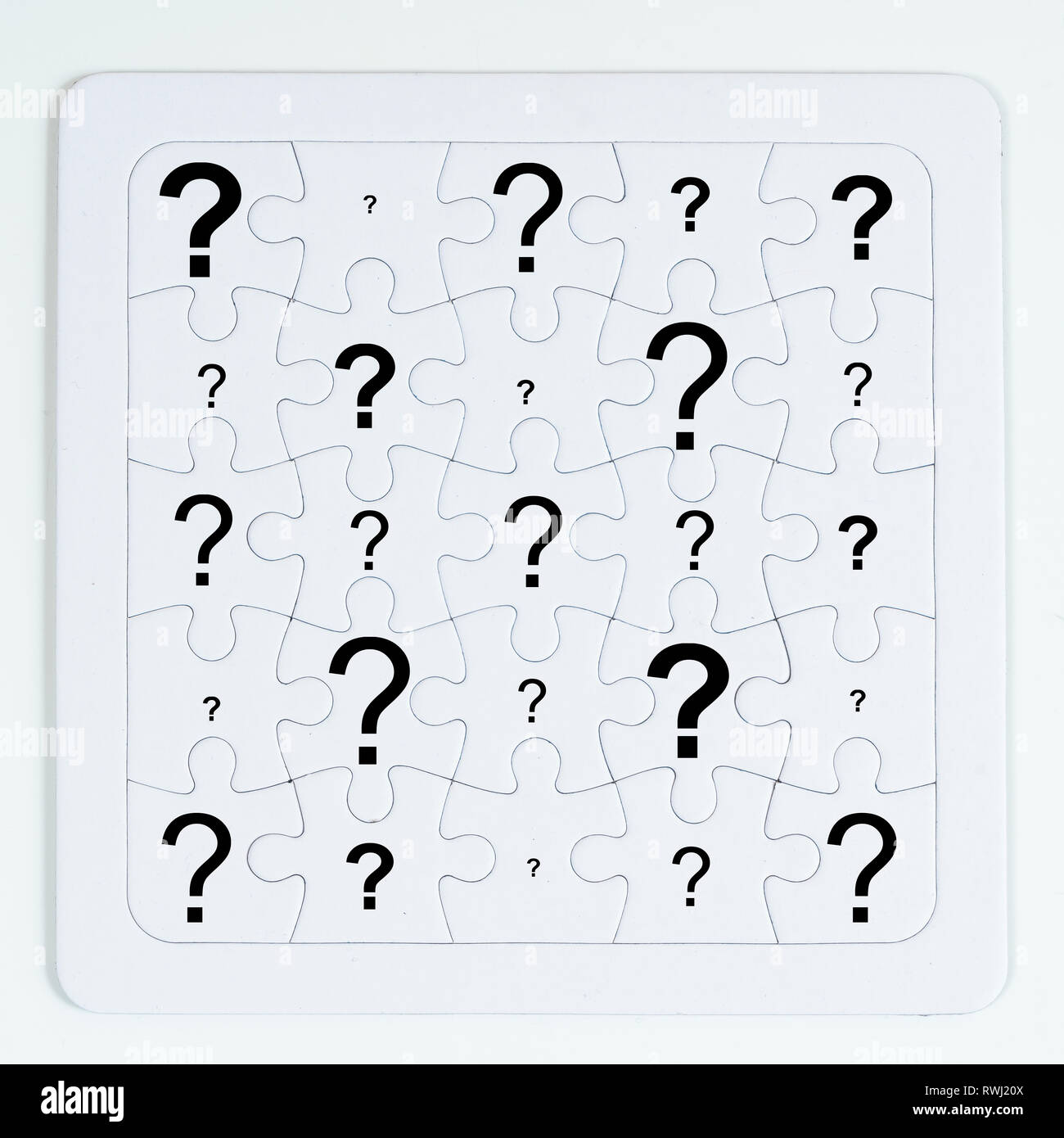 a puzzle with white pieces with an question mark - Stock Image