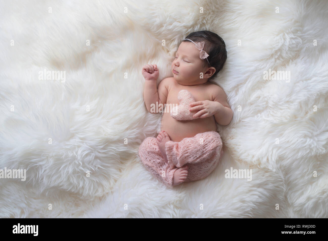 Sleeping week old newborn baby girl wearing light pink knitted pants and holding a tiny heart shaped pillow shot in the studio on a white sheepski