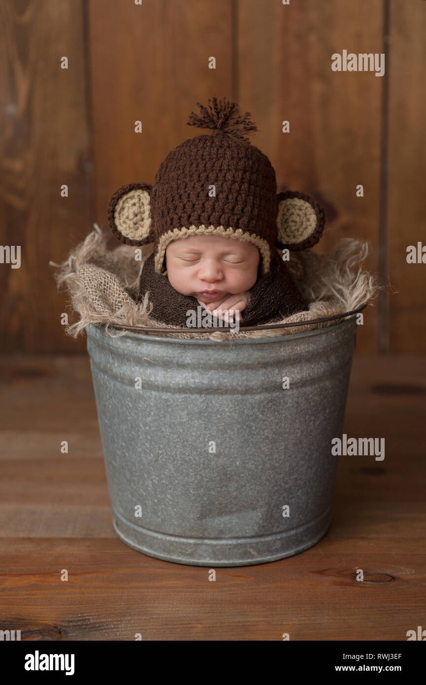 One week old newborn baby boy wearing a brown, crocheted monkey hat and sleeping in a galvanized steel bucket. Shot in the studio on a wood background. - Stock Image