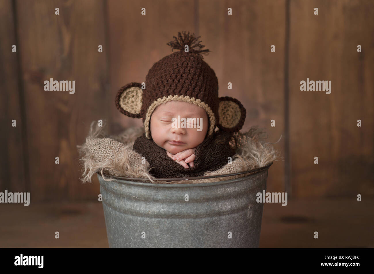 One week old newborn baby boy wearing a brown, crocheted monkey hat. He is sleeping in a galvanized steel bucket and has a slight grin on his face. - Stock Image
