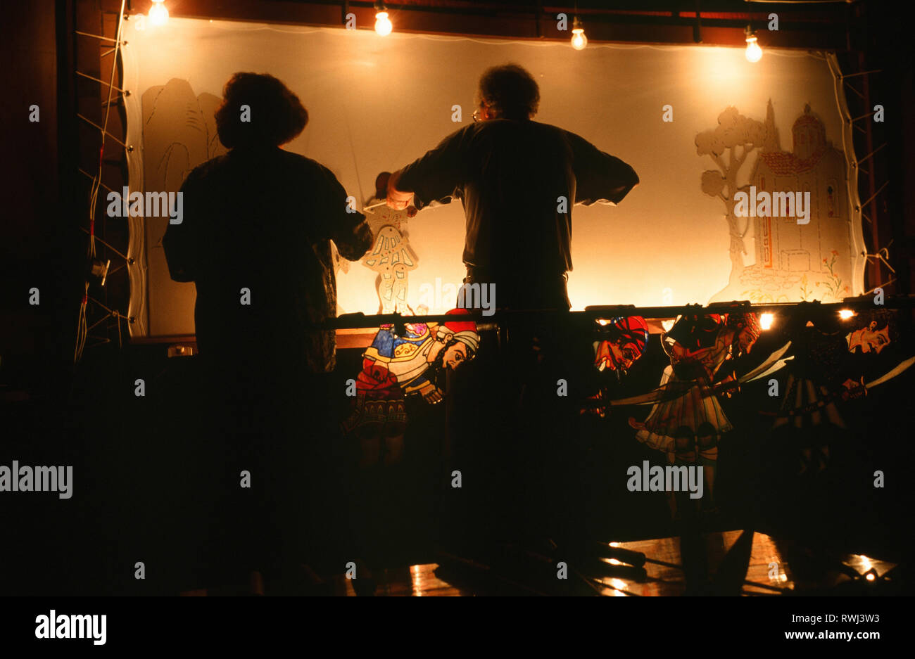 Backstage during a performance of the traditional Greek shadow puppet theatre known as Karaghiozi after its scheming, comic, central character. - Stock Image