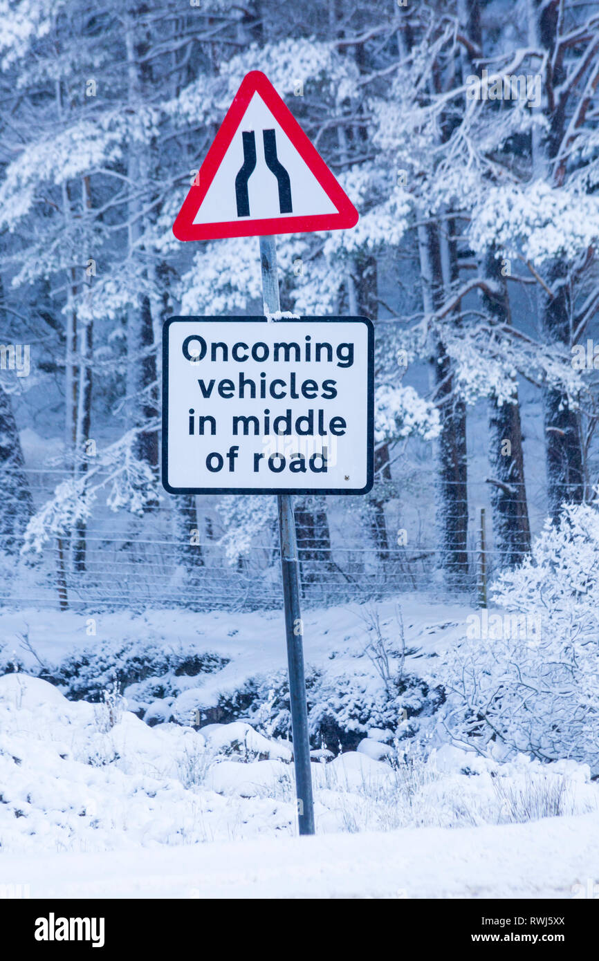 Oncoming vehicles in middle of road & road narrows on both sides road signs on A82 road on a cold winter morning at Rannoch Moor, Argyll, Scotland - Stock Image