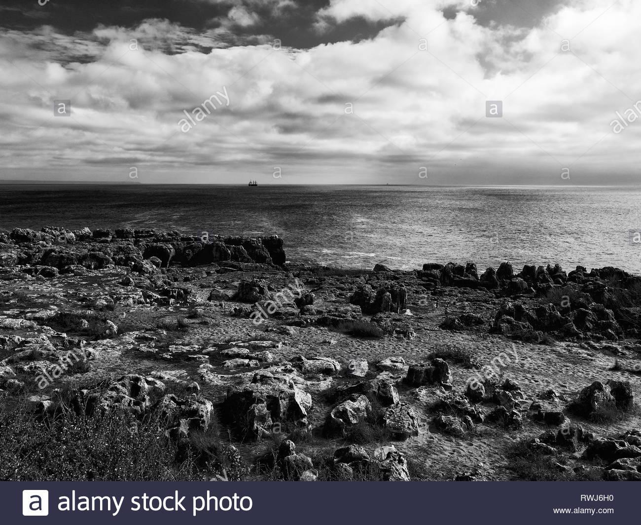 Cargo ship anchored off-shore, B&W black and white, Cascais, Portugal - Stock Image