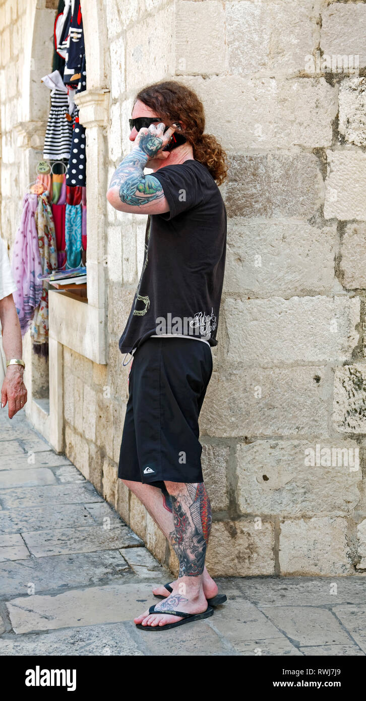 heavily tattooed man, talking on cell phone; long hair; pony tail, black clothes; skin decorations, Old Town; Dubrovnik; Croatia; Europe; summer; vert - Stock Image