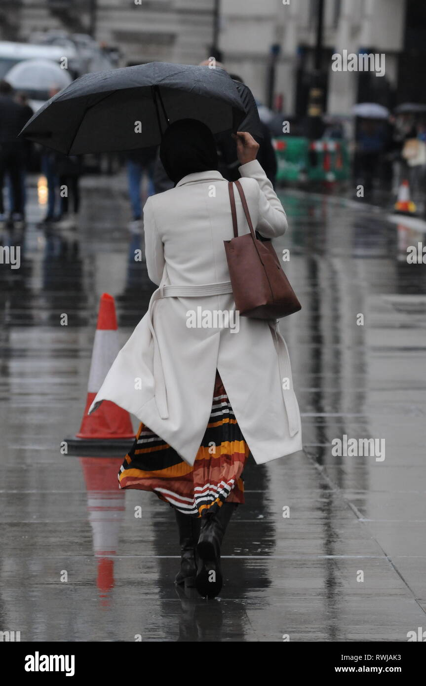 London, UK, 6 March 2019  Midweek showers in Trafalgar Square London.  Credit: JOHNNY ARMSTEAD/Alamy Live News - Stock Image