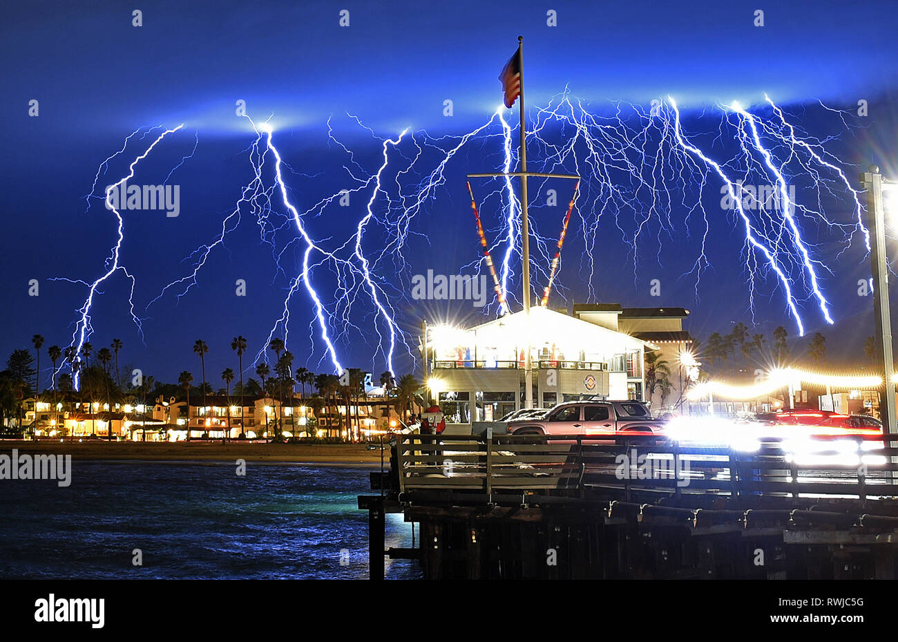 Los Angeles, California, USA. 6th Mar, 2019. A time exposure captures a series of lightning strikes above Stearns Wharf in Santa Barbara. An atmospheric river fueled winter storm slammed the region with heavy rain, hail and thunderstorms overnight, producing a stunning lightning shows in the Southern California sky. The latest storm in Californias wet winter, which dumped heavy rain on Santa Barbara County overnight, moved into Los Angeles County and orange counties Wednesday. Credit: Mike Eliason/Santa Barbara County Fire/ZUMA Wire/Alamy Live News - Stock Image