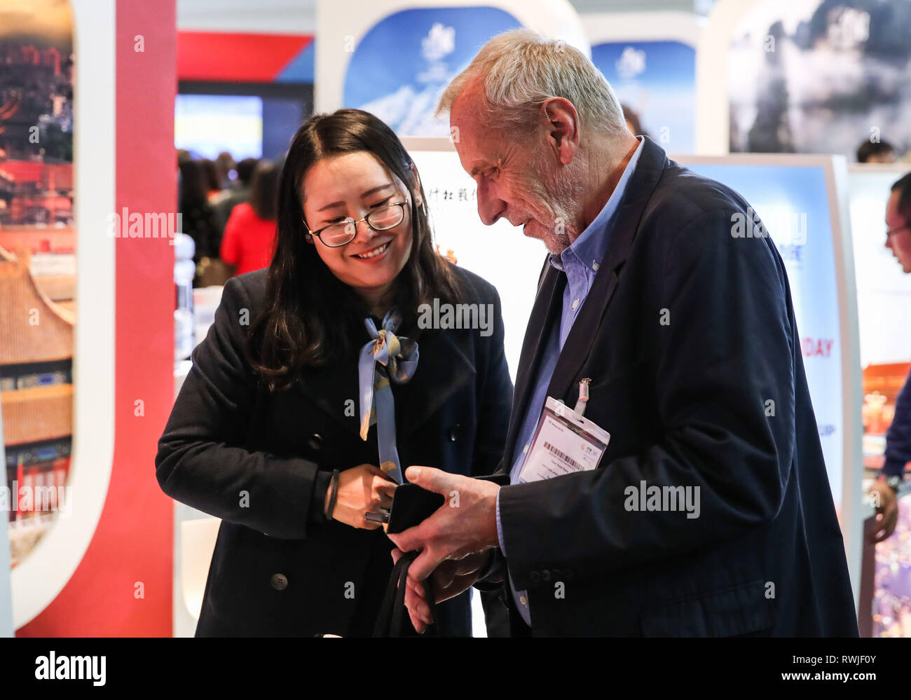 Berlin, Germany  6th Mar, 2019  A visitor talks with a staff member