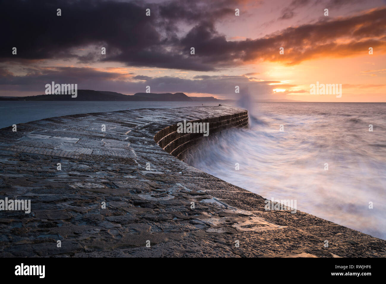 Lyme Regis, Dorset, UK.  7th March 2019. UK Weather.  Clouds building at sunrise above the Cobb Harbour wall at Lyme Regis in Dorset before a band of heavy showers came in.   Picture Credit: Graham Hunt/Alamy Live News - Stock Image