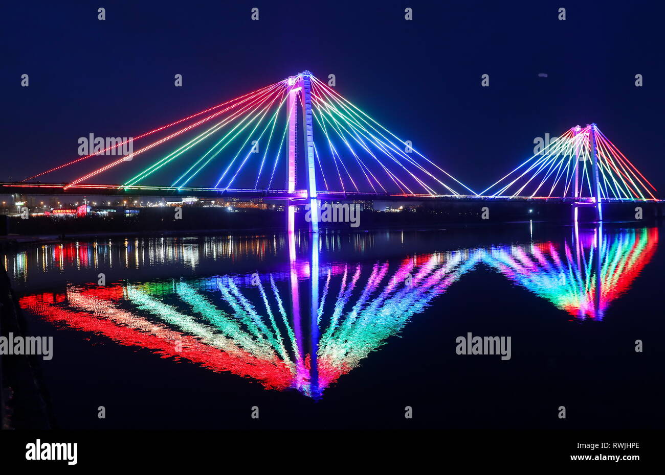 Krasnoyarsk, Russia. 06th Mar, 2019. KRASNOYARSK, RUSSIA - MARCH 6, 2019: A view of Vinogradovsky Bridge, a cable-stayed foot and cycle bridge over the Yenisei River in Krasnoyarsk, illuminated for a light and music show as part of the 2019 Winter Universiade. Peter Kovalev/TASS Credit: ITAR-TASS News Agency/Alamy Live News - Stock Image