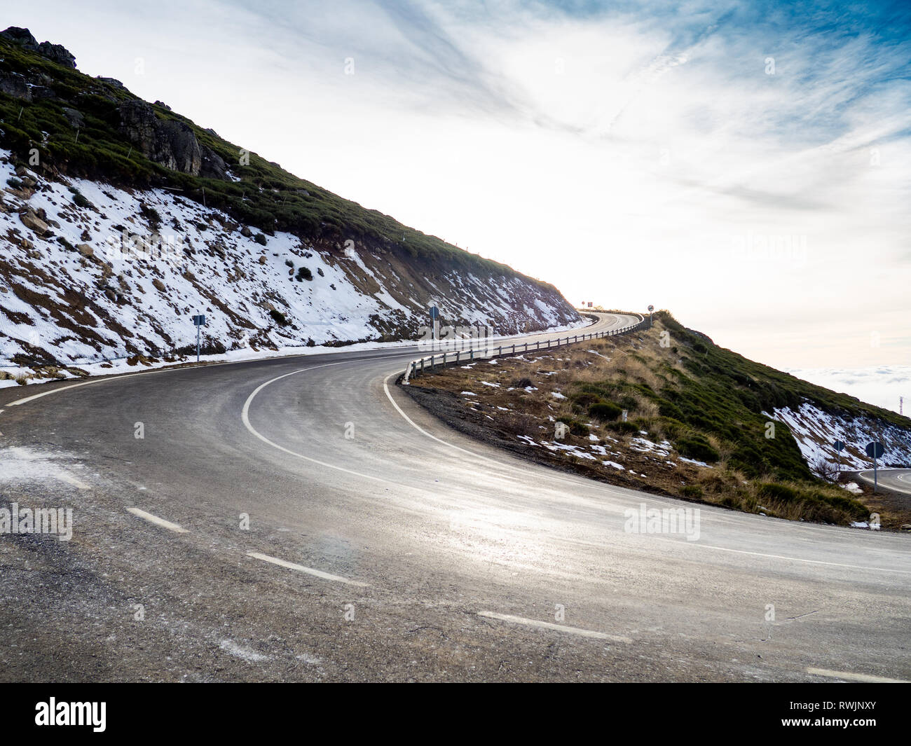 Very closed curve on a dangerous high mountain road with cloudy skies and snow on La Covatilla, Bejar (Salamanca) - Stock Image