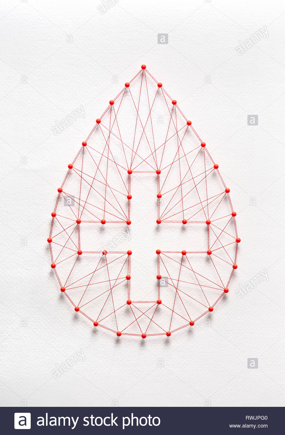 Donate blood concept. Network of pins and threads in the shape of a blood drop symbolising group effort and collaboration for saving lives. - Stock Image
