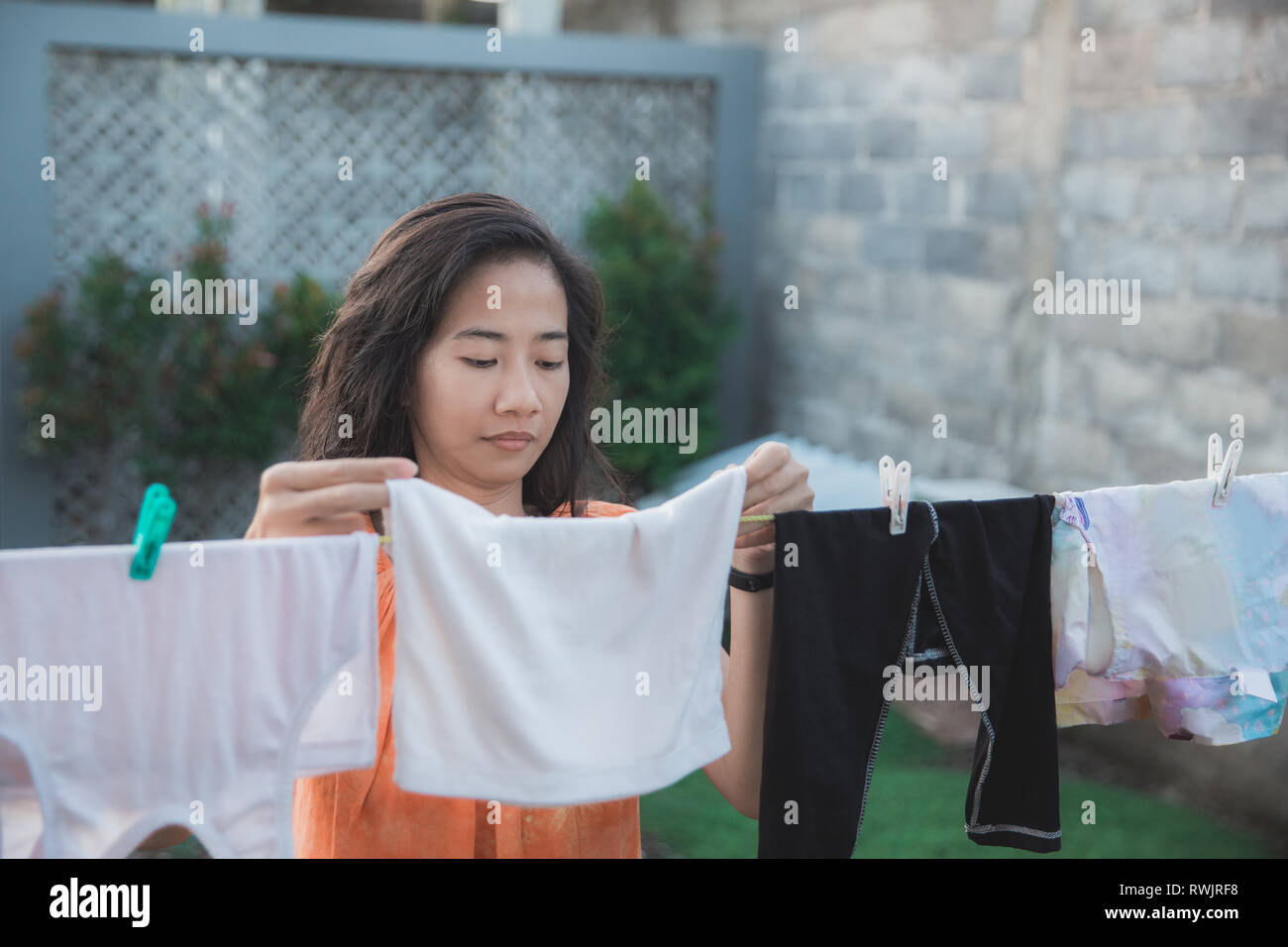 portrait of a housewife drying clothes in the morning - Stock Image